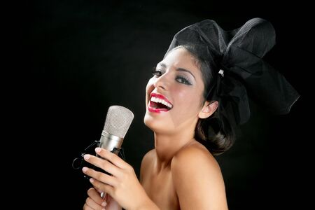 Beautiful woman singing on a vintage microphone on black background photo