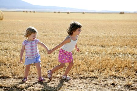Girls playing with the round wheat dried bales outdoor summer Stock Photo - 5641747