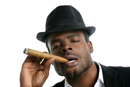 smoking a cigar: African american man smoking cigar portrait with black hat Stock Photo