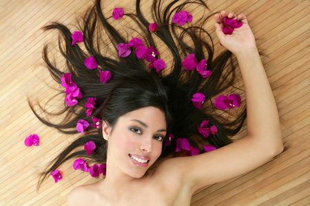 Beautiful indian woman portrait in a beauty spa with bougainvillea flowers photo