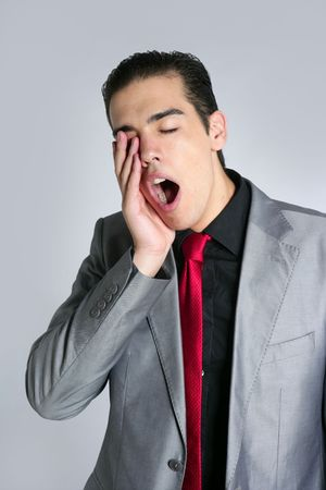 Businessman yawn boring on gray background with suit and red tie photo