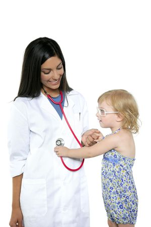 Brunette pediatric doctor with blond little girl on medical exam photo