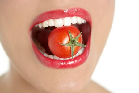 lips close up: Eating a red tomato macro of woman teeth and red lips mouth Stock Photo