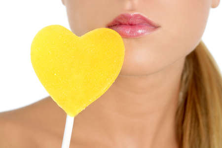 Heart shape candy on beautiful woman macro mouth photo