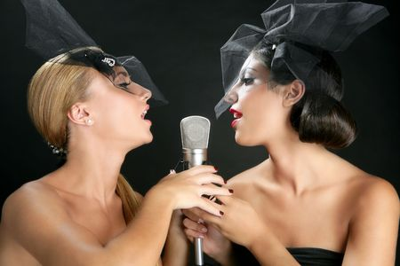 Beautiful women couple singing on a vintage microphone on black background Stock Photo - 5675243