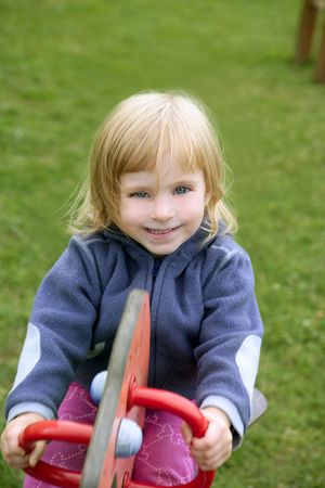 Blond adorable little girl playing on the playground photo