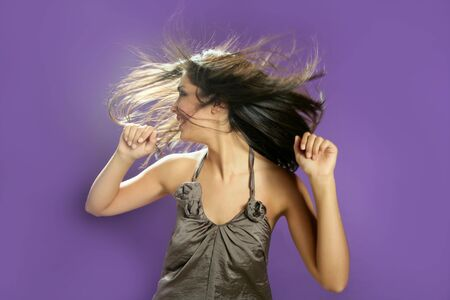 Brunette indian beautiful woman dancing at studio on purple background photo