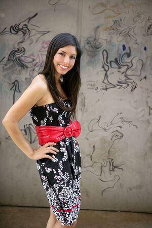 Beautiful brunette urban woman posing on city graffiti background photo