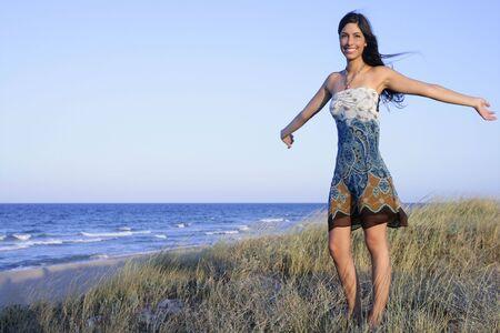 Beautiful brunette posing free with sunset sun on the beach photo
