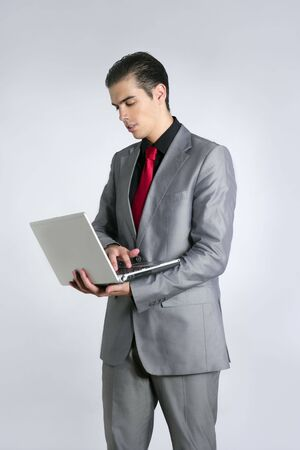 Businessman in gray suit holding laptop computer at studio Stock Photo - 5725209
