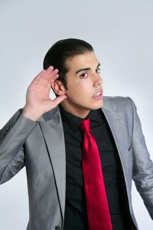 deafness: Businessman with hand in ear as a deafness sign gesture Stock Photo