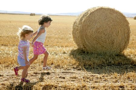 Girls playing with the round wheat dried bales outdoor summer Stock Photo - 5725129