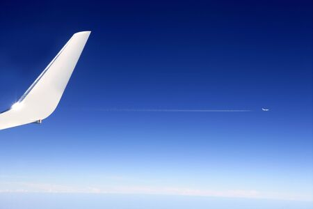 Aircraft wing detail flying high up in deep blue sky photo