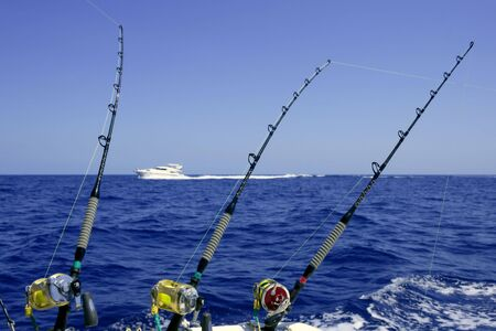 Blue sea and sky in a big game tuna fishing day rods and reels on boat. photo