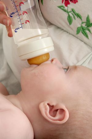 Baby blond little girl feeding drinking milk in a bottle photo