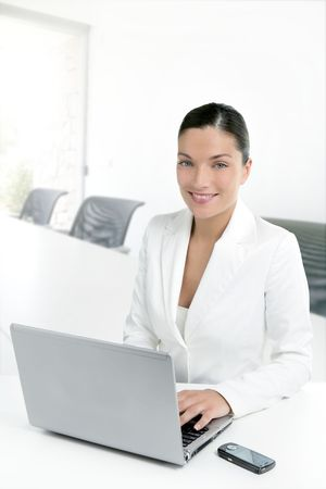 Modern businesswoman working in white office with laptop computer photo