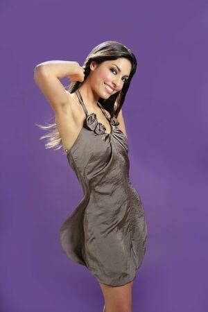 Brunette indian beautiful woman dancing at studio on purple background photo