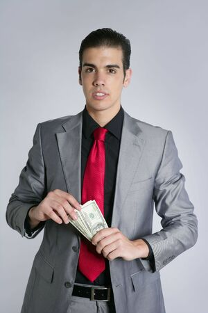 Businessman young with dollar notes suit and tie on gray background photo