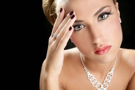Blond elegant thinking fashion woman with jewelry on black photo