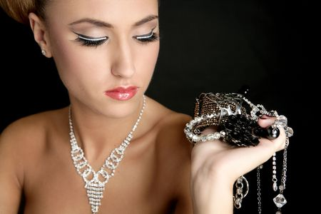 Ambition and greed in fashion woman with jewelry in hands on black background photo