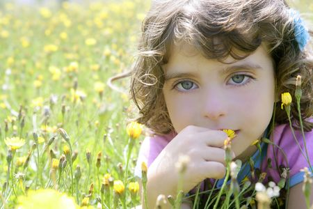 Adorable little girl smell flower in the country meadow photo
