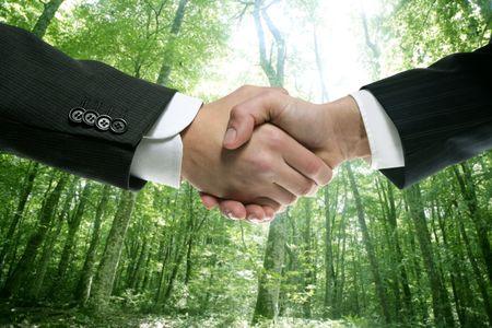 apreton de manos: Hombre de negocios ecol�gicos apret�n de manos en un fondo de bosque verde