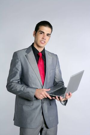 Businessman in gray suit holding laptop computer at studio photo