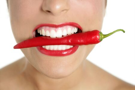 lips close up: Beautiful woman teeth eating red hot chili pepper