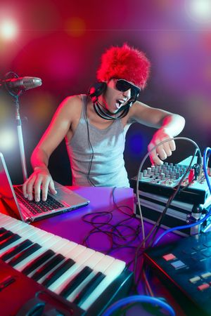 Dj with colorful light and music mixing digital equipment photo