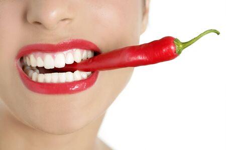 Beautiful woman teeth eating red hot chili pepper