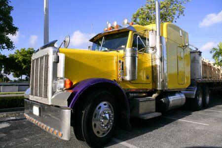 trucker: Big yellow american truck in sunny blue sky day
