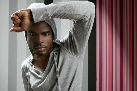 African american man with gray hood over wallpaper background photo