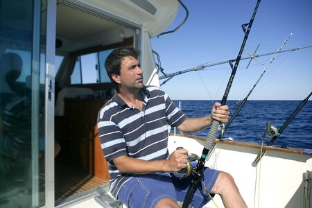 Angler big game saltwater fisher boat with rods and reels photo