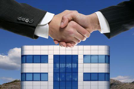 Businessman handshake over mirror building sky mountains photo