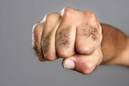 the hairy: Hairy man fisht closeup expression over gray background Stock Photo
