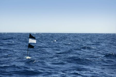 Blue ocean with longline flag fishing floating beacon in Spain photo