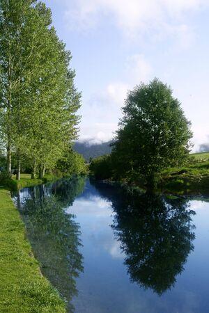 reflexion: Reflexi�n de R�o Azul en un bosque con cielo azul suave  Foto de archivo