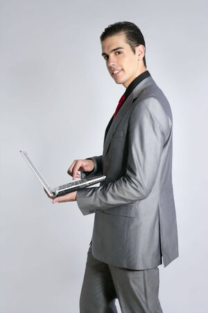Businessman in gray suit holding laptop computer at studio Stock Photo - 5994057