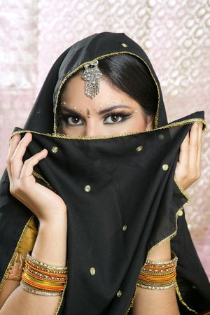Beautiful brunette asian girl with black veil on face, traditional indian costume photo