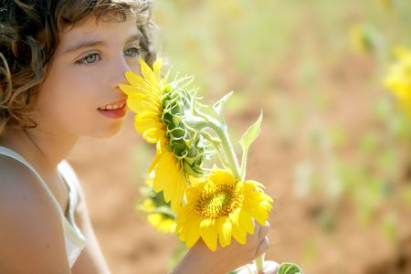 Beautiful little girl in a summer sunflower colorful field photo