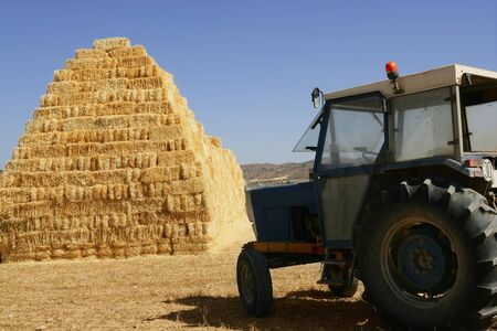 Barn stacked with piramyd shape and agriculture tractor vehicle photo