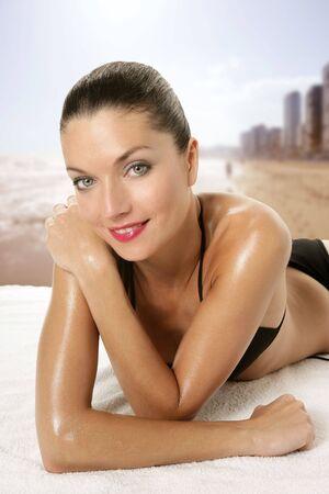 Beautiful sexy woman with red lips and black bikini posing at the beach photo