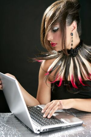Attractive brunette fashion woman with laptop over black photo
