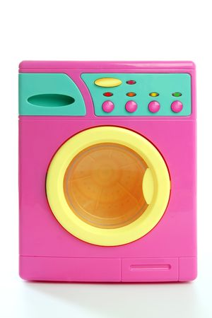 Colorful pink yellow clothes toy washing machine isolated on white photo