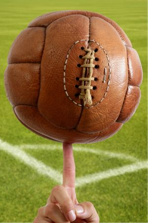 Aged vintage retro football leather ball in man hand grass field photo