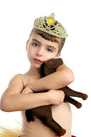 Beautiful children little ballerina girl hug her brown toy horse photo