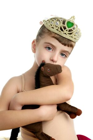 Beautiful children little ballerina girl hug her brown toy horse photo