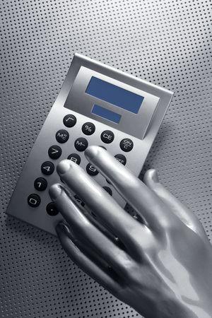 business futuristic silver hand metaphor on calculator keyboard photo