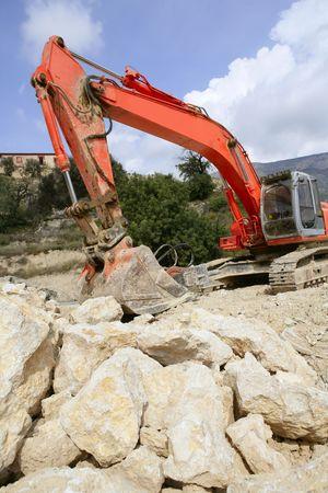 Backhoe bulldozer working hard with stones  photo