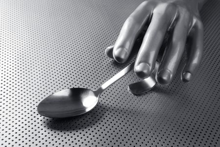 gray silver hand and spoon futuristic food modern metaphor photo